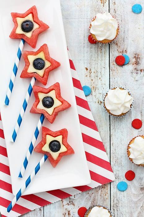 """<p>Cookie cutters turn <a href=""""http://www.bakersroyale.com/fruit/fourth-of-july-dessert-fruit-pops"""" class=""""link rapid-noclick-resp"""" rel=""""nofollow noopener"""" target=""""_blank"""" data-ylk=""""slk:watermelon, apples, and blueberries"""">watermelon, apples, and blueberries</a> into a healthy holiday dessert. Striped straws add to the appeal.</p> <p><small class=""""source"""">S</small></p>"""