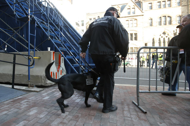 A Boston police officer and security dog pass by the photo bridge at the finish line for the 118th Boston Marathon Monday, April 21, 2014 in Boston. (AP Photo/Elise Amendola)