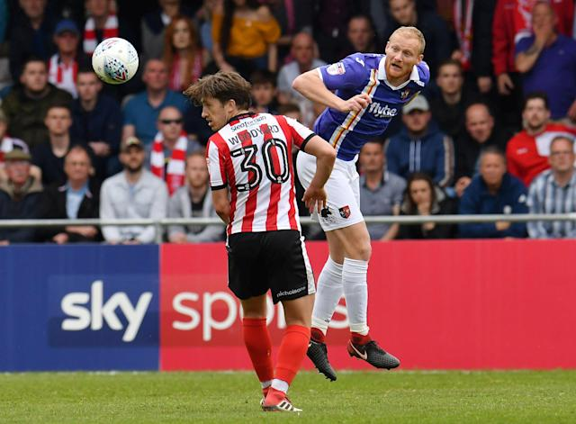 "Soccer Football - League Two Play Off Semi Final First Leg - Lincoln City v Exeter City - Sincil Bank, Lincoln, Britain - May 12, 2018 Exeter City's Robbie Simpson in action with Lincoln City's Alex Woodyard Action Images/Paul Burrows EDITORIAL USE ONLY. No use with unauthorized audio, video, data, fixture lists, club/league logos or ""live"" services. Online in-match use limited to 75 images, no video emulation. No use in betting, games or single club/league/player publications. Please contact your account representative for further details."