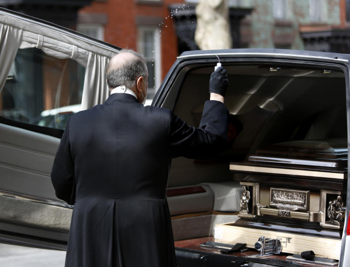 Monsignor Kieran Harrington, Vicar for Communications for the Diocese of Brooklyn, splashes holy water over the casket of the Rev. Jorge Ortiz-Garay in the Brooklyn borough of New York as they prepare to transport his body to John F. Kennedy International Airport on Sunday, May 3, 2020. At 49, Ortiz-Garay was the first Catholic cleric in the United States to die from the coronavirus outbreak. He will be laid to rest in his birthplace of Mexico City. (AP Photo/Jessie Wardarski)