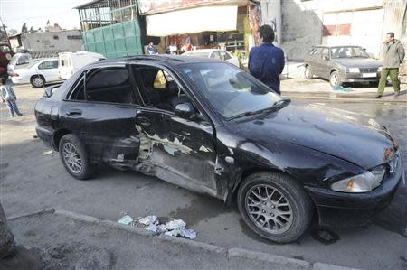 A damaged car is pictured after a mortar shell hit a textile factory at al-Dweil'a neighbourhood in Damascus
