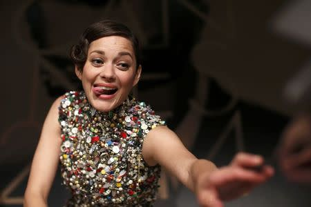 """Cast member Marion Cotillard reacts as she signs autographs at the end of a news conference for the film """"Deux jours, une nuit"""" in competition at the 67th Cannes Film Festival in Cannes"""