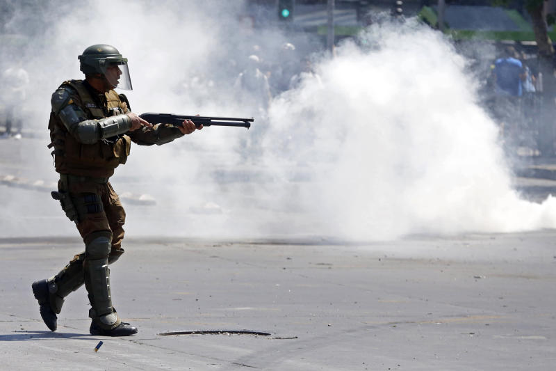 A police officer fires rubber pellets at protesters as a state of emergency remains in effect in Santiago, Chile, Sunday, Oct. 20, 2019. Protests in the country have spilled over into a new day, even after President Sebastian Pinera cancelled the subway fare hike that prompted massive and violent demonstrations. (AP Photo/Luis Hidalgo)