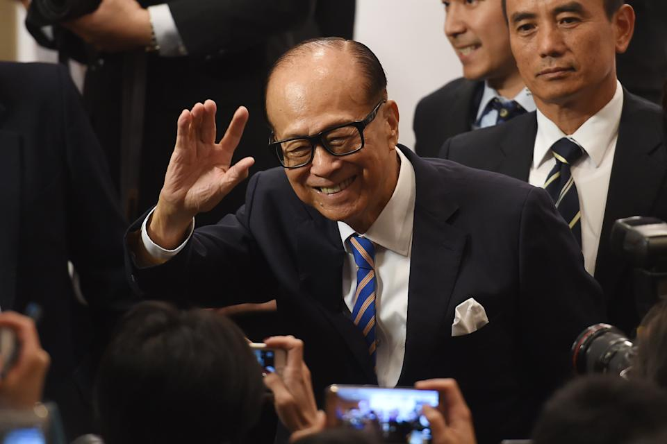 Hong Kong's richest man Li Ka-shing (L), 89, waves as he leaves a press conference in Hong Kong on March 16, 2018. Hong Kong's richest man Li Ka-shing announced on March 16 he was stepping down as chairman of his flagship company CK Hutchison, marking the end of an era for one of the world's most storied tycoons. Li, who is turning 90 in July this year, has finally concluded mounting speculation about his retirement as he is expected to hand over the reins to his eldest son Victor. / AFP PHOTO / Anthony WALLACE        (Photo credit should read ANTHONY WALLACE/AFP via Getty Images)