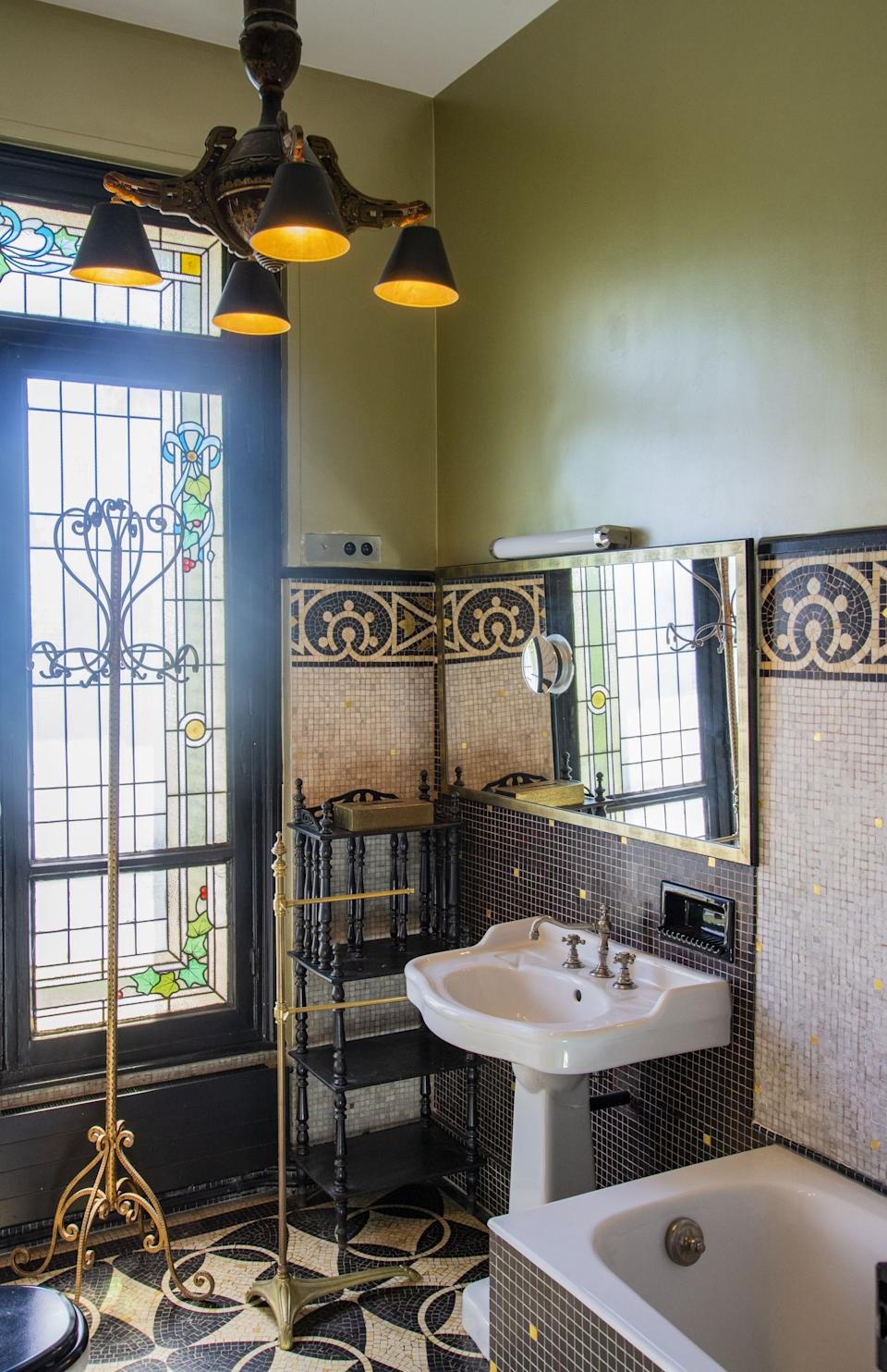 """<div class=""""caption""""> All of the decoration is original to the apartment. On the walls of a bathroom are marble mosaics, and the stained-glass window is early 20th-century. The walls are lacquered paint and the chandelier is 19th-century, found at the flea market in the South of France, L' Isle sur la Sorgue. The coatrack is in gilded iron, circa 1950, by Italian designer Pier Luigi Colli. </div>"""