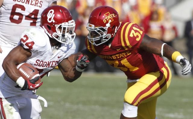 AMES, IA- NOVEMBER 3: Running back Brennan Clay #24 of the Oklahoma Sooners rushes up field during the third quarter against defensive end Rony Nelson #31 of the Iowa State Cyclones on November 3, 2012 at Jack Trice Stadium in Ames, Iowa. Oklahoma defeated Iowa State 35-20. (Photo by Matthew Holst/Getty Images)