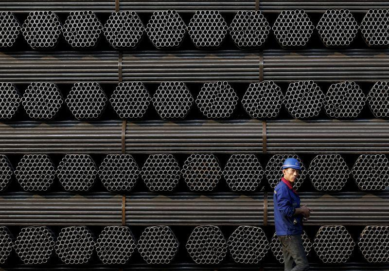 File photo of a worker walking past a pile of steel pipe products at the yard of Youfa steel pipe plant in Tangshan in China's Hebei Province