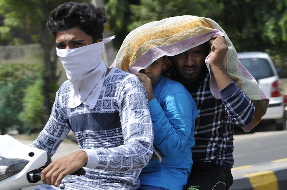 NOIDA, INDIA - JUNE 10: Boys on a two-wheeler cover themselves with a cloth to beat the heat on a summer day on June 10, 2019 in Noida, India. The mercury shattered all records in Delhi NCR on Monday with parts of the national capital region recording an all-time high of 48 degrees Celsius for the month of June. (Photo by Sunil Ghosh/Hindustan Times via Getty Images)