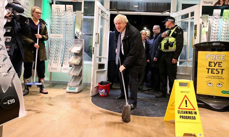 Boris Johnson mops the floor to help with the clean-up at an opticians in Matlock