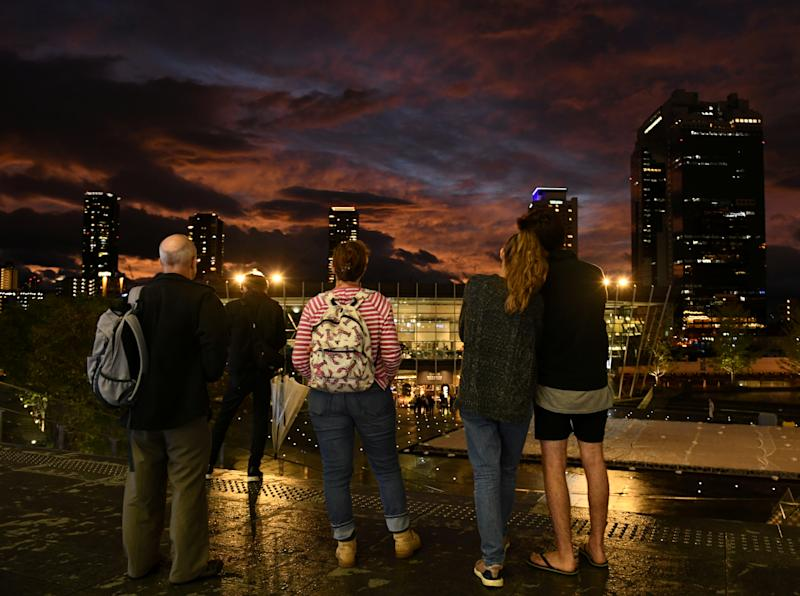 People look at clouds during sunset near Osaka Station, as typhoon 'Hagibis' approaches Japan, in Osaka, Japan Oct. 12, 2019. (Photo: Annegret Hilse/Reuters)