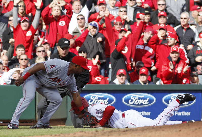 Cincinnati Reds' Ryan Ludwick is safe at third base ahead of the tag by Los Angeles Angels third baseman Alberto Callaspo, left, in the third inning of a major league baseball game, Monday, April 1, 2013, in Cincinnati. Ludwick left the game with a dislocated shoulder on the play. (AP Photo/David Kohl)