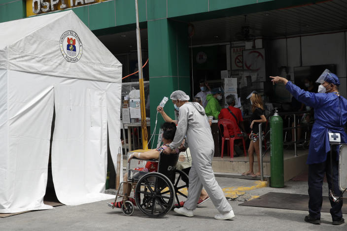 A health worker wearing a protective suit pushes a COVID-19 patient to an isolation tent outside a hospital in Manila, Philippines on Monday, April 26, 2021. COVID-19 infections in the Philippines surged past 1 million Monday in the latest grim milestone as officials assessed whether to extend a monthlong lockdown in Manila and outlying provinces amid a deadly spike or relax it to fight recession, joblessness and hunger. (AP Photo/Aaron Favila)