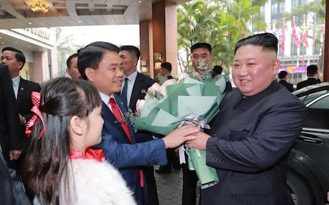 Kim Jong-un receives a bouquet of flowers as he arrives at the Melia hotel in Hanoi - Credit: KCNA/AFP