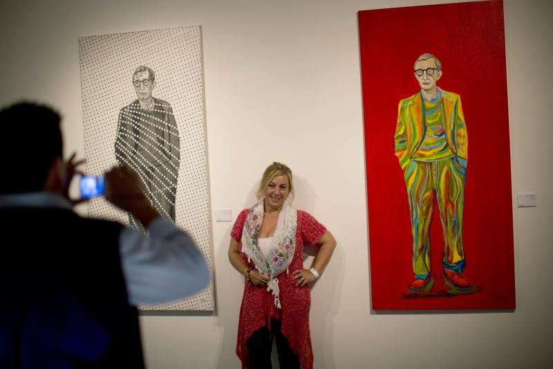 """A woman poses for a photography between paintings of U.S. director Woody Allen at an art exhibit titled """"Queremos tanto a Woody,"""" or """"We so love Woody"""" by Argentine artist Hugo Echarri in Buenos Aires, Argentina, Thursday, Feb. 6, 2014. The exhibit in honor of Allen was inaugurated just days after the artist faced renewed accusations that he molested Dylan Farrow, his then-7-year-old adopted daughter in 1992. (AP Photo/Rodrigo Abd)"""
