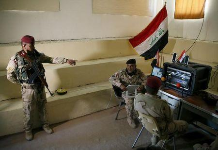 Iraqi soldiers work at a radio station at Makhmour base, Iraq