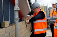 Britain's Prime Minister Boris Johnson tries his hand at bricklaying during a visit to a construction site in Warrington, north west England on August 6, 2020, as the government announce a major overhaul of planning policy in England. (Photo by PHIL NOBLE / POOL / AFP) (Photo by PHIL NOBLE/POOL/AFP via Getty Images)