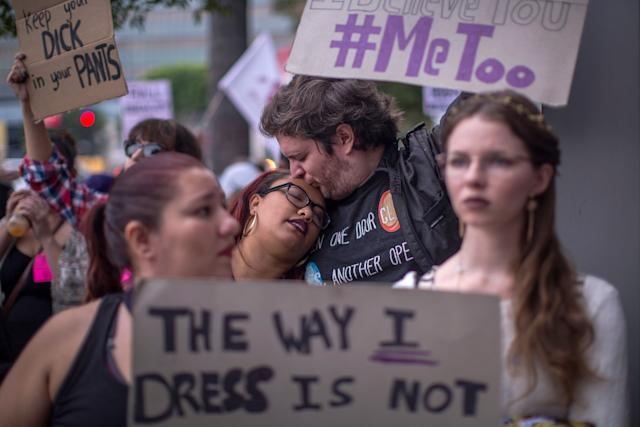 Protesters hold up signs denouncing sexual misconduct.