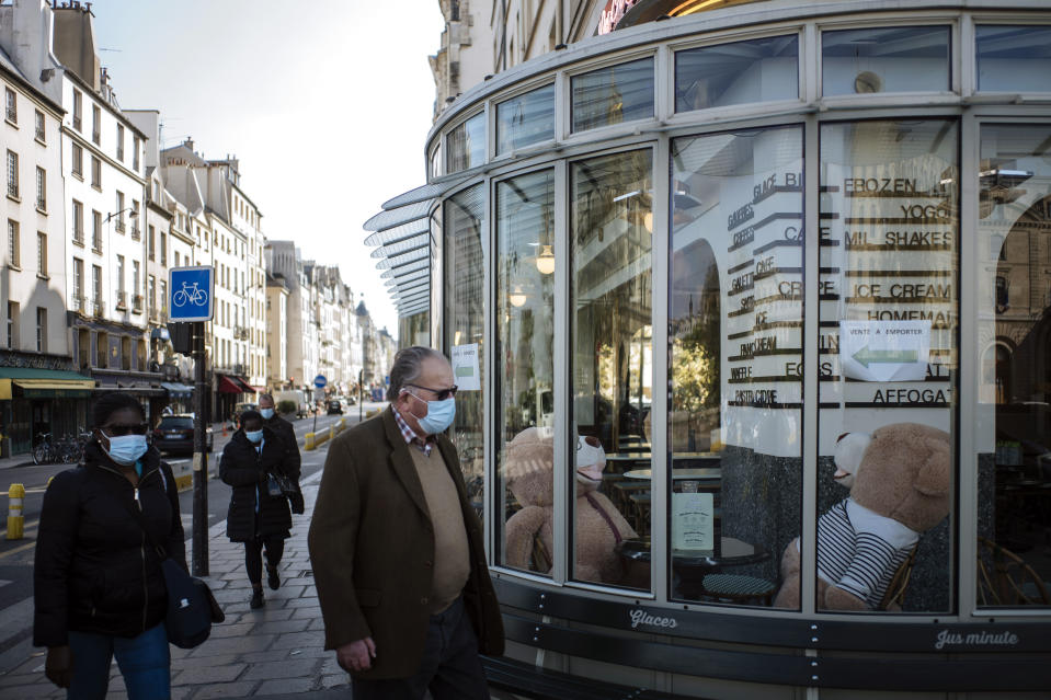 People, wearing face masks to prevent the spread of the coronavirus, walk past a closed restaurant with teddy bears inside, in Paris, Monday, April 19, 2021.(AP Photo/Lewis Joly)