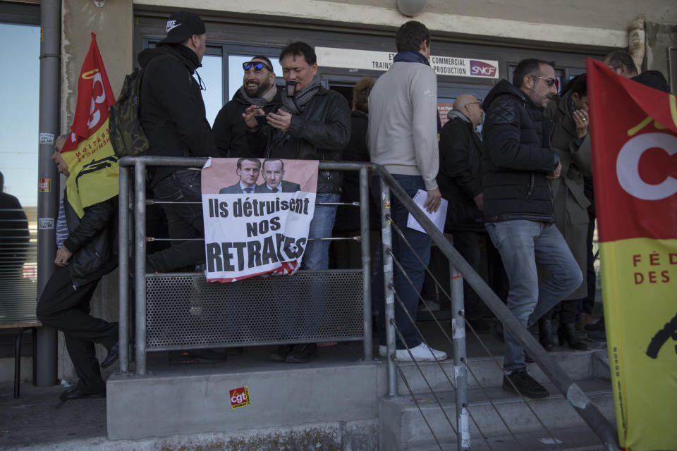 """Striking railway workers gather above a sign that reads: """"They destroy our Pensions"""", during a union general assembly meeting at the Gare St-Charles station in Marseille, southern France, Monday, Dec. 09, 2019. Paris commuters inched to work Monday through exceptional traffic jams, as strikes to preserve retirement rights halted trains and subways for a fifth straight day. (AP Photo/Daniel Cole)"""