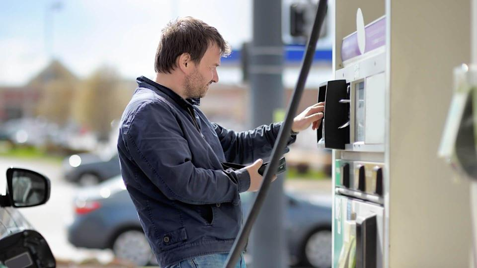 Man filling gasoline fuel in car holding nozzle.