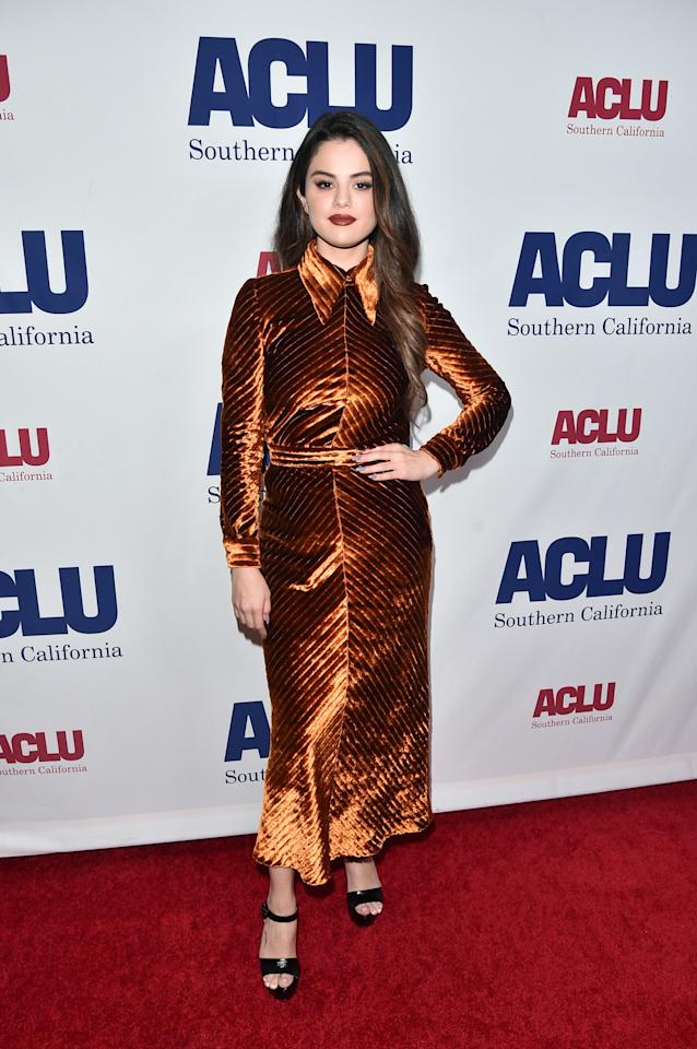 Selena was channeling major fall vibes with this dark orange dress and berry lipstick.