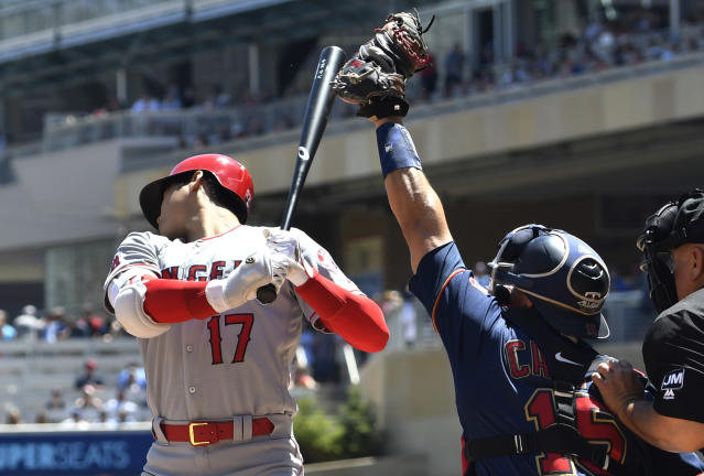 Los Angeles Angels' Shohei Ohtani, left, rears back on a pitch by Minnesota Twins pitcher Jake Odorizzi as Minnesota Twins catcher Jason Castro reaches high for the ball in the third inning of a baseball game Wednesday, May 15, 2019, in Minneapolis. (AP Photo/Jim Mone)