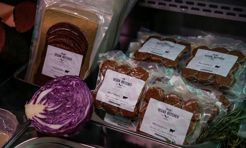 Close-up of a shelf of plastic-wrapped products including 'meatballs', with half a red cabbage placed as decoration