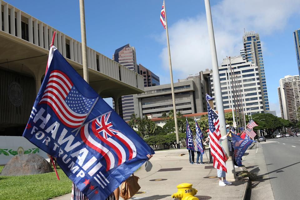 Demonstrators carry American and Trump campaign flags during a protest outside the Hawaii State Capitol in Honolulu on Jan. 6, 2021. Pro-Trump demonstrators have massed outside statehouses across the country, including in Hawaii.