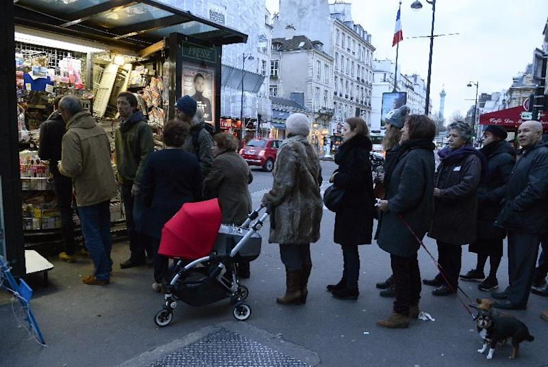 People queue outside a newsagent's kiosk in Paris, on January 14, 2015 (AFP Photo/Bertrand Guay)