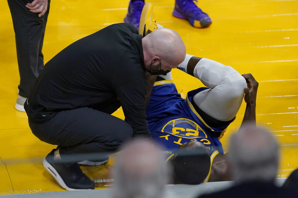 Golden State Warriors forward Draymond Green, right, receives medical attention during the first half of the team's NBA basketball game against the Brooklyn Nets in San Francisco, Saturday, Feb. 13, 2021. (AP Photo/Jeff Chiu)