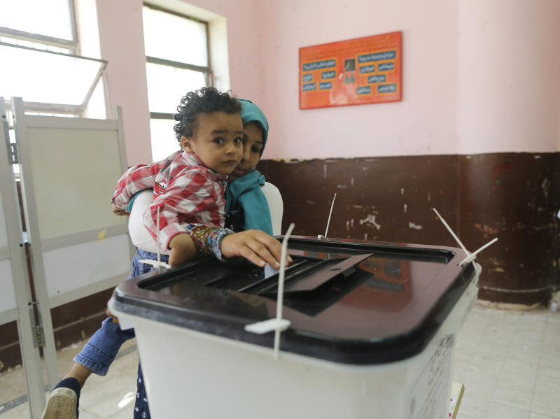 A voters carries her son as she casts her ballot on constitutional amendments during the first day of three-day voting at polling station in Cairo, Egypt, Saturday, April 20, 2019. Egyptians are voting on constitutional amendments that would allow el-Sissi to stay in power until 2030. (AP Photo/Amr Nabil)