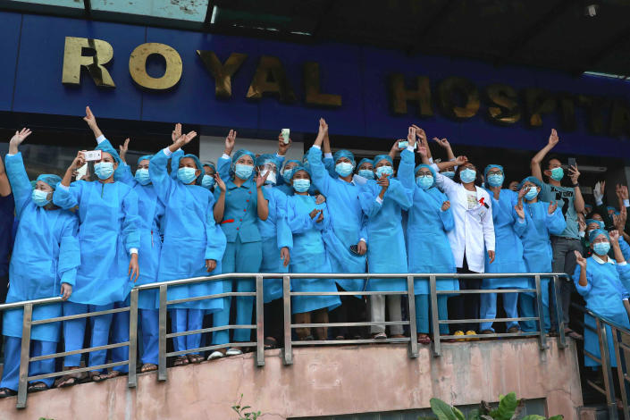 FILE - In this Sunday, Feb. 7, 2021 file photo, medical workers give the three-fingered salute outside Asia Royal Hospital as they watch protesters march in Yangon, Myanmar. Medics are particularly feared by the military because they are highly respected and well-organized, with a strong network of unions and professional groups. (AP Photo/File)