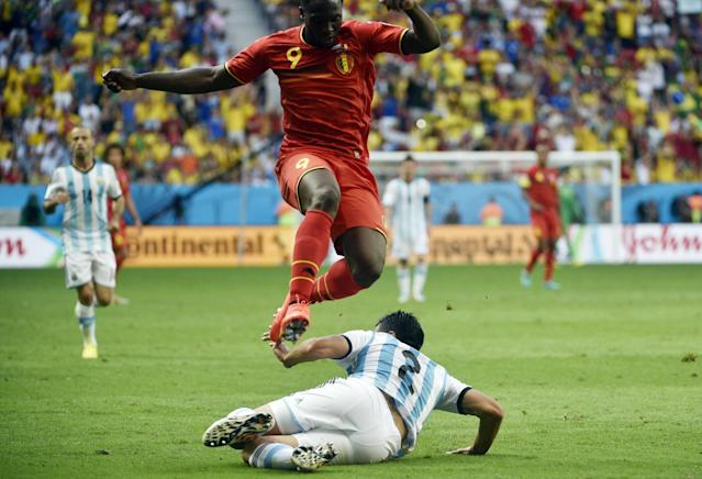 Belgium's Romelu Lukaku jumps over a tackle attempt from Argentina's Ezequiel Garay during a quarter-final match between Argentina and Belgium at the Mane Garrincha National Stadium in Brasilia during the 2014 FIFA World Cup on July 5, 2014 (AFP Photo/Martin Bureau)