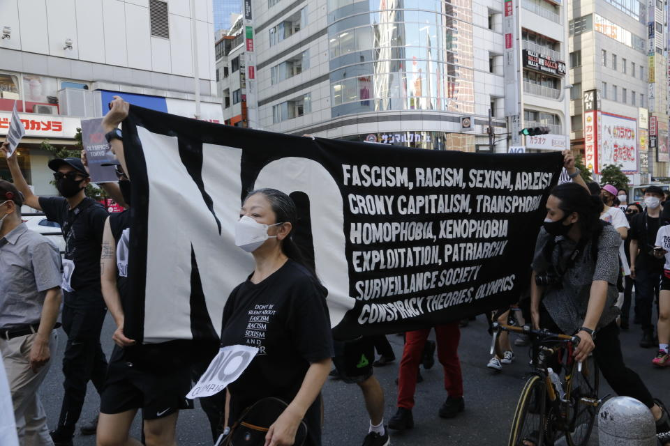 People march in Tokyo's Shinjuku shopping district Sunday, July 18, 2021, to protest against the Tokyo Olympics starting from July 23.(AP Photo/Yuri Kageyama)