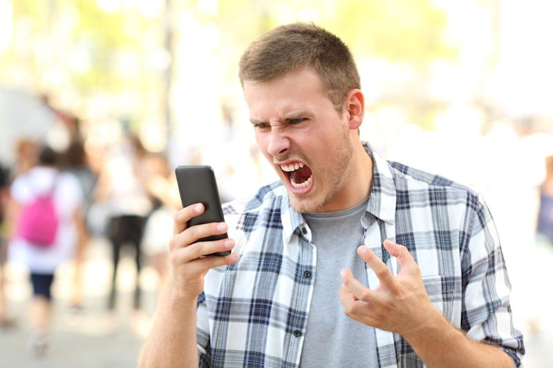 Young man yelling at his cell phone.