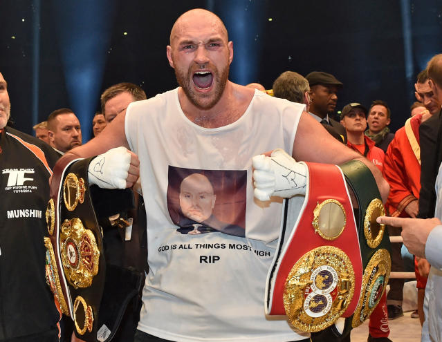 FILE - In this Nov. 29, 2015 file photo, Britain's new world champion Tyson Fury, celebrates with the WBA, IBF, WBO and IBO belts after winning the world heavyweight title fight against Ukraine's Wladimir Klitschko in Duesseldorf, western Germany. Tyson Fury is back in heavyweight boxing after nearly 2 1/2 years away. He credits some straight talk from fellow heavyweight boxer Deontay Wilder for getting him to return to the ring. Furys comeback fight is in Manchester, England, on June 9, 2018. (AP Photo/Martin Meissner, File)