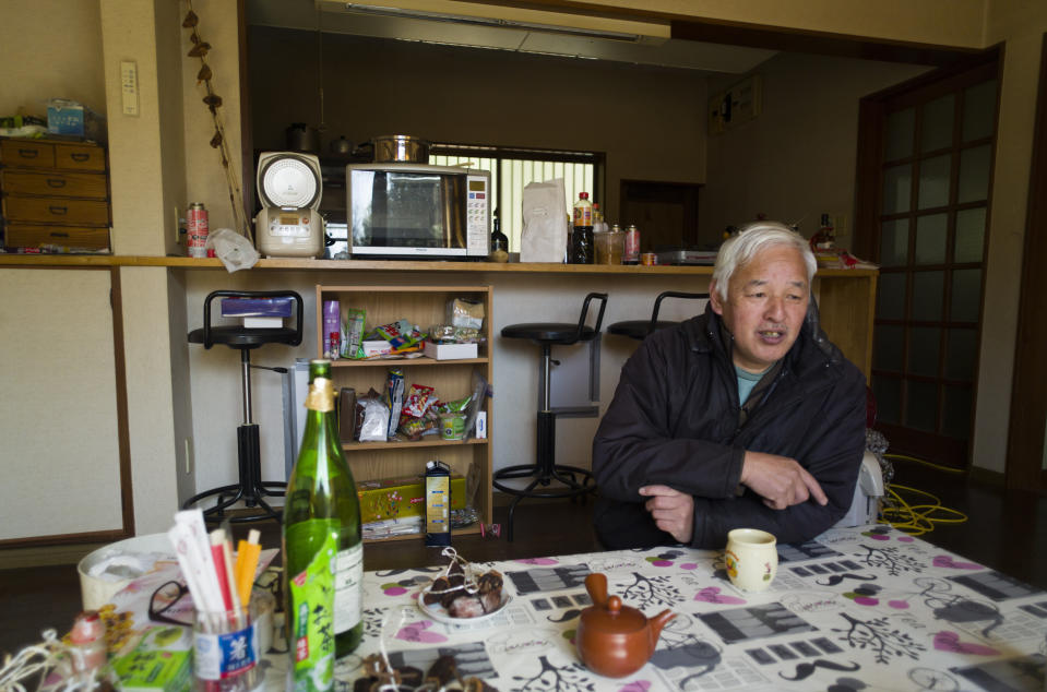 Naoto Matsumura speaks during an interview with The Associated Press at his home in Tomioka town, Fukushima prefecture, northeastern Japan, Sunday, Feb. 28, 2021. About 10 kilometers (6 miles) south of the wrecked Fukushima Dai-ichi nuclear power plant, rice farmer Matsumura defied a government evacuation order and stayed on his farm to protect his land the cattle abandoned by neighbors a decade ago. (AP Photo/Hiro Komae)
