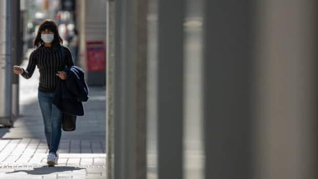 A woman wearing a mask walks through downtown Ottawa in April 2021 during the latest provincewide COVID-19 shutdown.