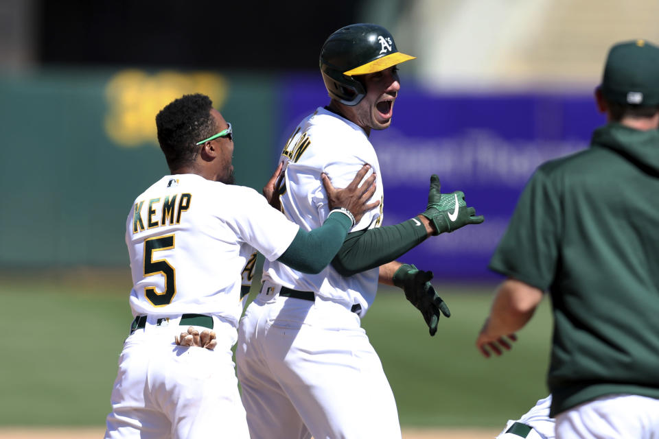 Oakland Athletics' Matt Olson, right, celebrates with teammate Tony Kemp, left, after driving in the winning run against the San Diego Padres during the 10th inning of a baseball game in Oakland, Calif., Wednesday, Aug. 4, 2021. (AP Photo/Jed Jacobsohn)