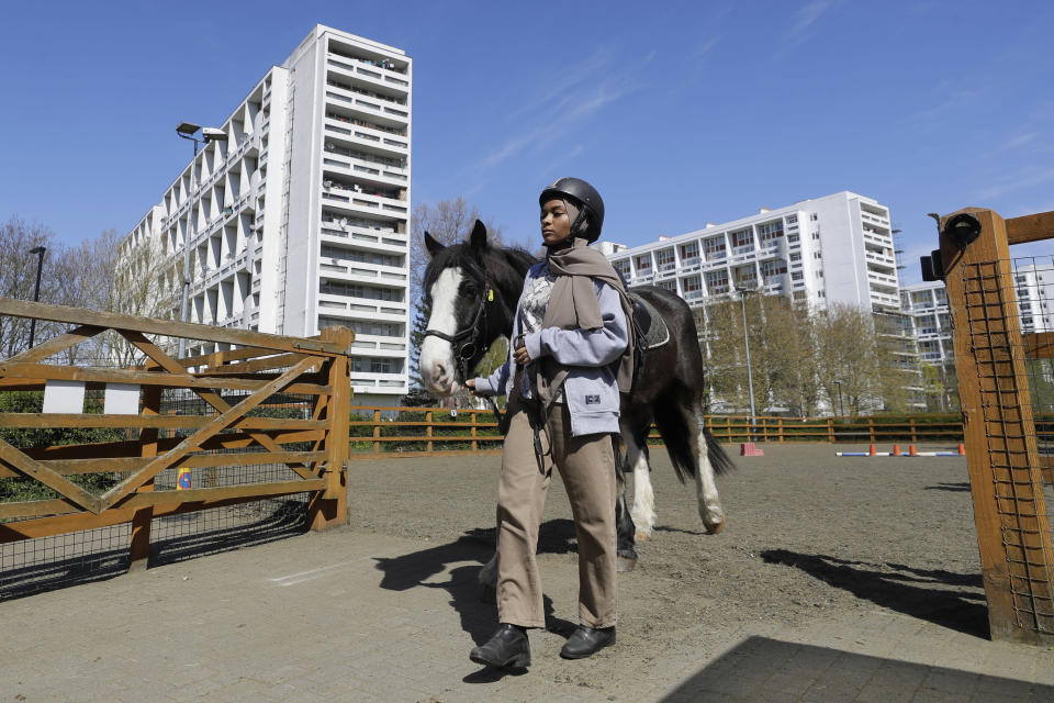 Tasneem Aly leads Bailey after a riding lesson at Ebony Horse Club in Brixton, south London, Sunday, April 18, 2021. In the midst of south London's hustle and bustle, only a 10-minute walk from a subway station, is a school where children are encouraged to horse around. The Ebony Horse Club provides 140 rides per week to children in the local community offering them the opportunity to learn important life skills along with horseback riding. (AP Photo/Kirsty Wigglesworth)