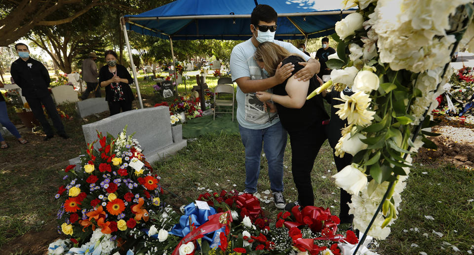 A man and a woman mourn at a gravesite of a coronavirus victim. Source: Getty