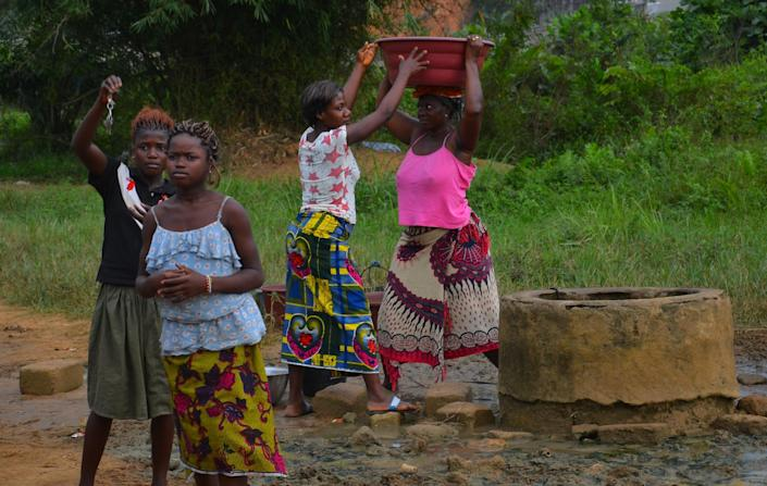 Women fetch water from a well near the site where two boys were attacked, in Yopougon, a suburb of Abidjan, on January 26, 2015 (AFP Photo/Herve Sevi)