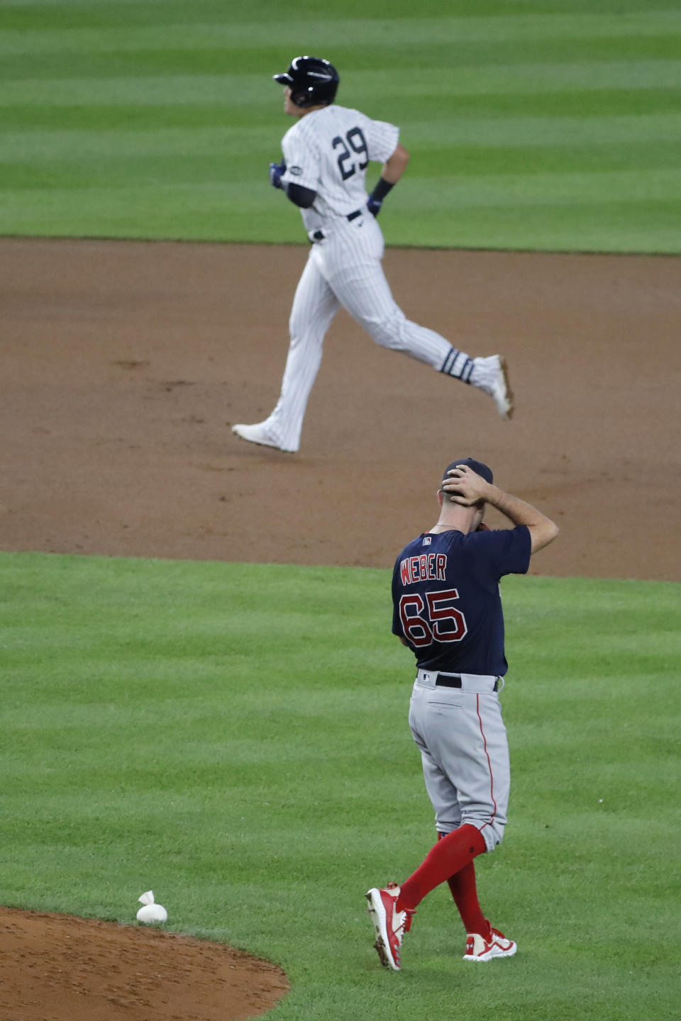 Boston Red Sox pitcher Ryan Weber, right, watches as New York Yankees' Gio Urshela, top, rounds the bases after hitting a home run during the fourth inning of a baseball game at Yankee Stadium, Friday, July 31, 2020, in New York. (AP Photo/Seth Wenig)