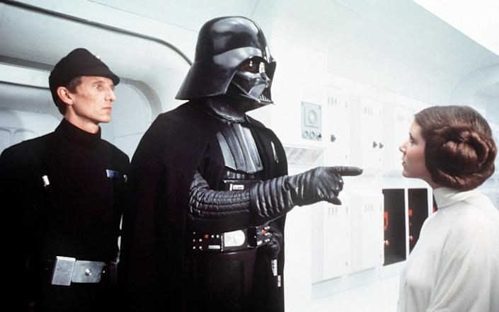 David Prowse as Darth Vader in Star Wars: Episode IV - A New Hope (1977), with Al Lampert and Carrie Fisher who revealed that the cast had nicknamed Prowse 'Darth Farmer' -  CAP/KFS