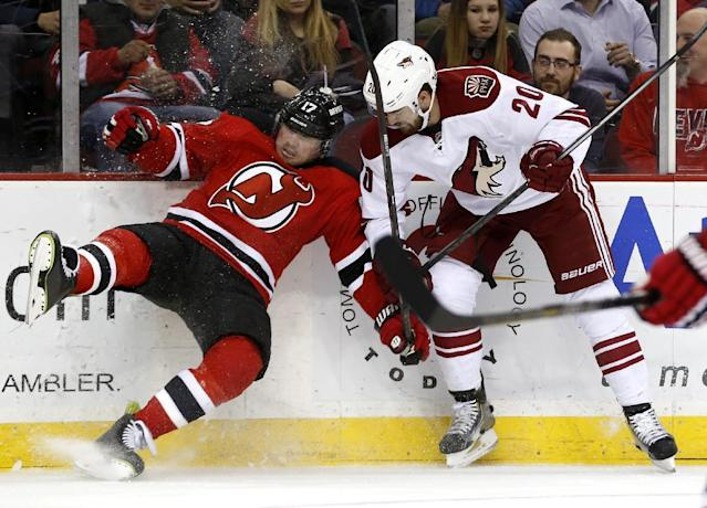 New Jersey Devils right wing Michael Ryder, left, falls to the ice while challenging Phoenix Coyotes defenseman Chris Summers for the puck during the second period of an NHL hockey game, Thursday, March 27, 2014, in Newark, N.J. (AP Photo/Julio Cortez)
