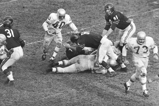 "FILE - In this Dec. 14, 1959, file photo, Detroit Lions back Howard Cassady (40) shoots toward a big hole in the Chicago Bears defense during the third quarter of a football game Chicago, Ill. Cassady, a Heisman Trophy winner and former NFL running back, died early Friday, Sept. 20, 2019, in Tampa, Fla., Jerry Emig, the Ohio State associate athletic director said. He was 85. Cassady played both football and baseball at Ohio State in the early 1950s, winning the Heisman Trophy in 1955. He also played 10 seasons in the NFL, mostly with the Detroit, and got the nickname ""Hopalong"" from local sports writers after the black-hatted Western star of the 1950s. (AP Photo/Ed Maloney, File0"