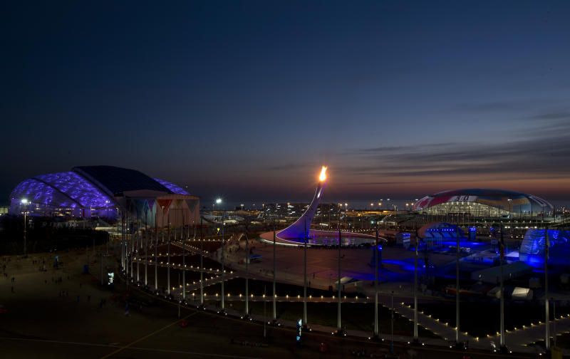 The Olympic flame burns at sunset before the closing ceremony of the 2014 Winter Olympics, Sunday, Feb. 23, 2014, in Sochi, Russia. (AP Photo/Matt Slocum)