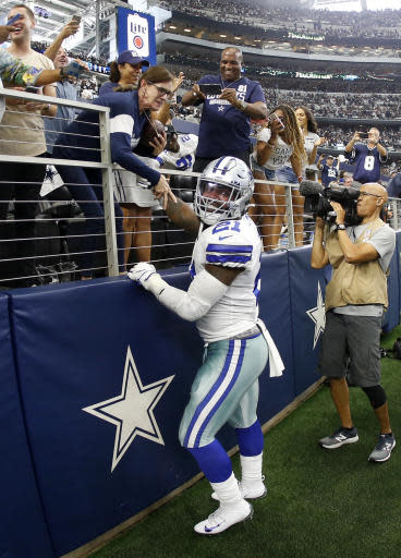 Dallas Cowboys' Ezekiel Elliott (21) smilers after giving away the ball he ran for a touchdown in the second half of a NFL football game against the New York Giants in Arlington, Texas, Sunday, Sept. 8, 2019. (AP Photo/Ron Jenkins)