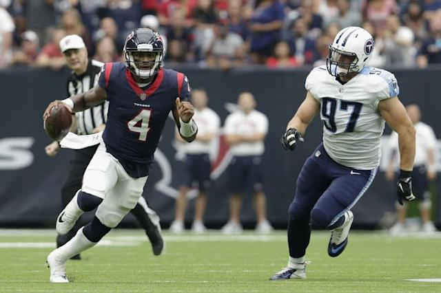 Deshaun Watson of the Houston Texans scrambles pursued by Karl Klug of the Tennessee Titans in the third quarter, at NRG Stadium in Houston, Texas, on October 1, 2017 (AFP Photo/Tim Warner)