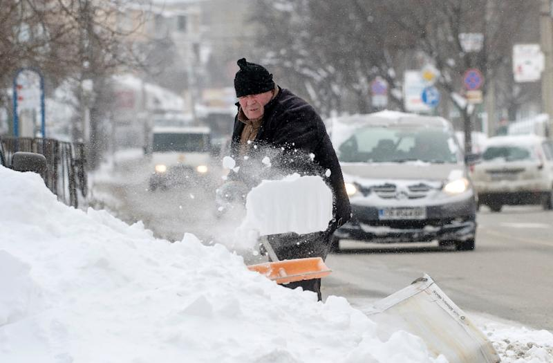 A man digs a car out of the snow in a suburb of the Bulgarian capital Sofia after heavy snowfall on January 7, 2017